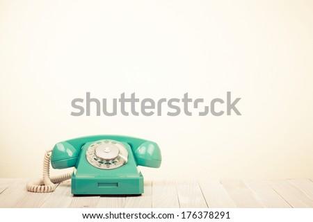 Retro rotary telephone on wooden table - stock photo