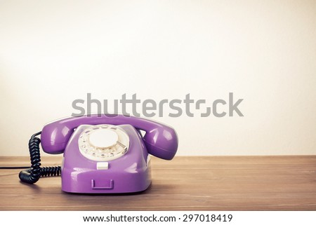 Retro rotary telephone on wooden table. Old style filtered photo - stock photo
