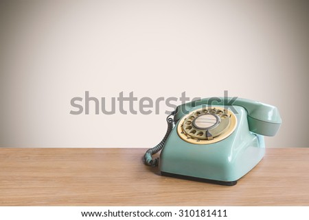 Retro rotary telephone on wooden table with pastel background - stock photo