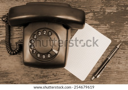 Retro rotary telephone with paper and pen on wooden background - stock photo