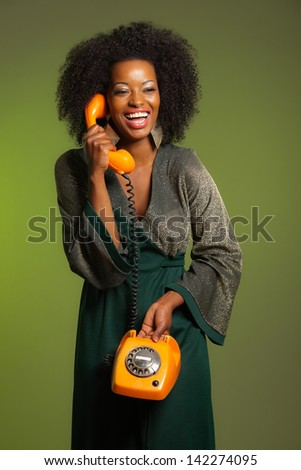 Retro 70s afro fashion woman with green dress. Calling with orange phone. Green wall.