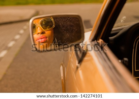 Retro 70s afro fashion woman with sunglasses looking in mirror of brown seventies car. - stock photo