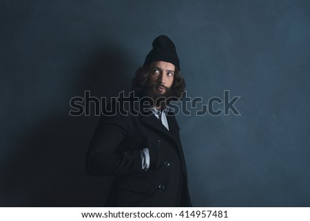 Retro 1970s beard man with long hair wearing black coat and woolen cap. Standing against gray wall. - stock photo