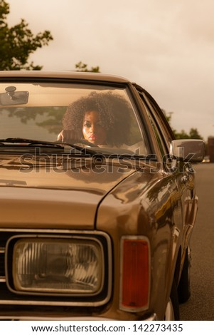 Retro 70s fashion african american woman driving in gold seventies car. - stock photo