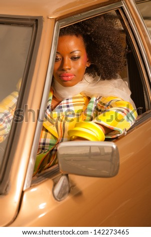 Retro 70s fashion african american woman driving in gold seventies car.