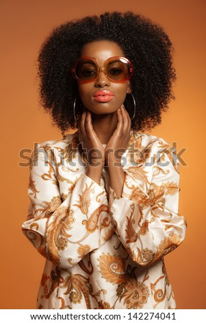 Retro 70s fashion african woman with paisley dress and sunglasses. Brown background.