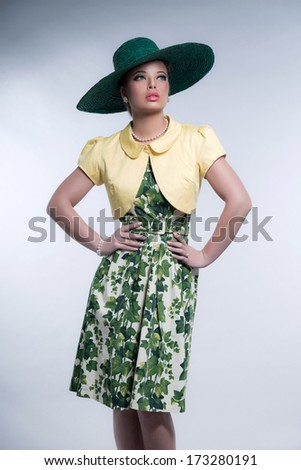 Retro 50s fashion brunette girl with hat wearing green dress and yellow blouse. Studio shot against grey. - stock photo