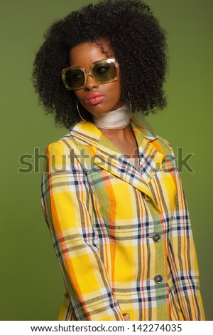 Retro 70s fashion style african woman with sunglasses. Yellow jacket and green background.