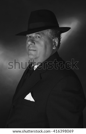 Retro 1930s gangster wearing hat. Classic black and white portrait.