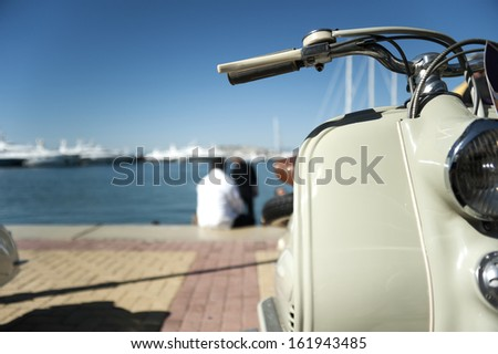 Retro scooter detail parked at a marina - stock photo