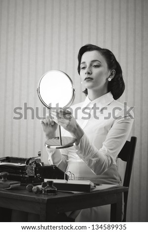 Retro secretary checking her make up on while on her workplace, she is holding a mirror - stock photo