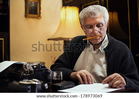 Retro Senior man writer with glasses and pencil in his mouth sitting at the desk and reading some text for writing on Obsolete Typewriter. - stock photo
