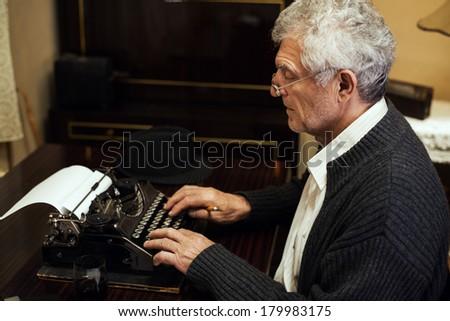 Retro Senior man writer with glasses writing on Obsolete Typewriter. - stock photo