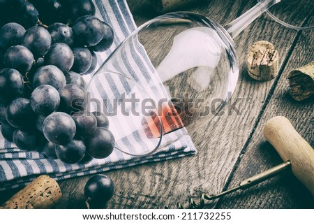 Retro setting with empty wine glass and grapes - stock photo