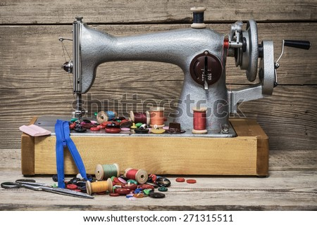 Retro sewing machine on a wooden background - stock photo