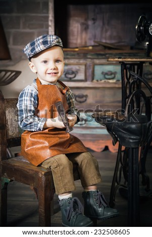 retro shot of a smiling little boy with hammer imitating the cobbler - stock photo