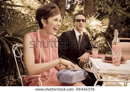 retro sixties style fashion couple having breakfast outdoor - stock photo
