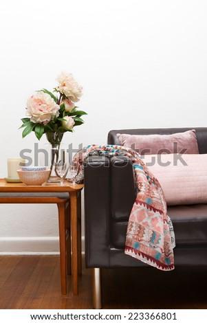 Retro sofa interior with accessories flowers cushions - stock photo
