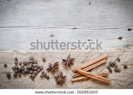 Retro spices background - cinnamon, pepper and anice on burlap and wood
