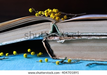 Retro spring still life - stack of worn books with yellow mimosa flowers. Selective focus at the book spines.   - stock photo