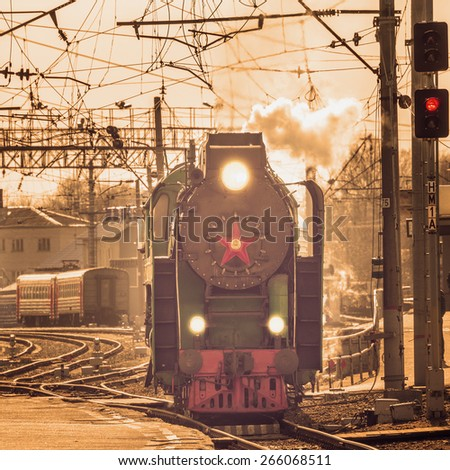 Retro steam train arrives to the station at day time. - stock photo