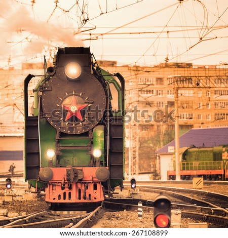Retro steam train moves on the station at sunset. - stock photo