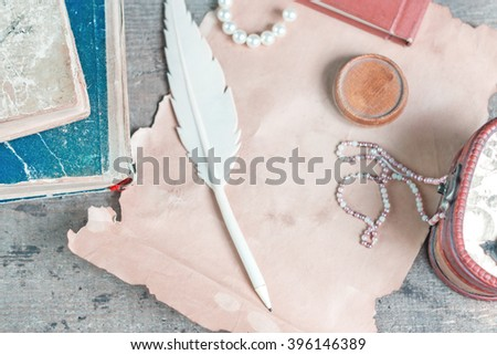 Retro still life with casket, old papers and books on a wooden table. Top view