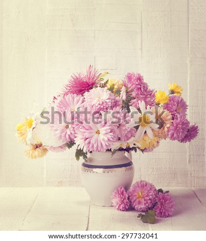 Retro still life with colourful chrysanthemums bunch on old  wooden board. Toned image - stock photo