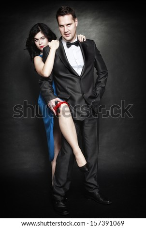 Retro style attractive couple in love, rich gangster and charming woman with gun on black background