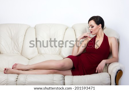 Retro style brunette woman lying on white sofa