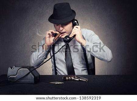 retro style criminal man using his vintage phone on grunge background - stock photo