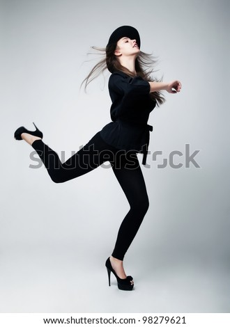 Retro style. Fashion Model Pin-up Girl in Black Clothing Running in studio - stock photo