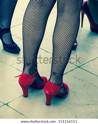 Retro style. Heart shape tattoo on sexy legs, vintage shoes and fishnet pantyhose. Aged photo. - stock photo