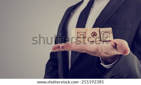 Retro style image of a businessman holding three wooden cubes with contact symbols - envelope, at sign and telephone - conceptual of communication and business support. - stock photo