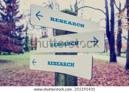 Retro style image of a signboard with the word Research with arrows pointing in three directions conceptual of there being many opportunities, components and elements. - stock photo