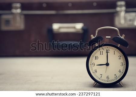 retro style image of alarm clock showing nine with vintage suitcase on the background. closeup. - stock photo