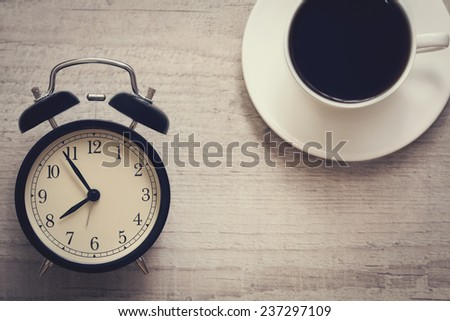 retro style image of alarm clock showing seven fifty five with cup of coffee on the wooden background. top view. - stock photo