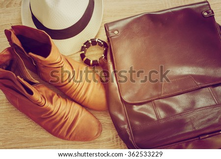 Retro style image of female fashion: straw hat, leather bag and shoes over white wooden background. Selective focus, shallow DoF, vintage filters. - stock photo