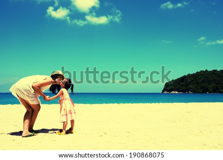Retro style In summer vacation. Young mother and her kid playing on the beach - stock photo