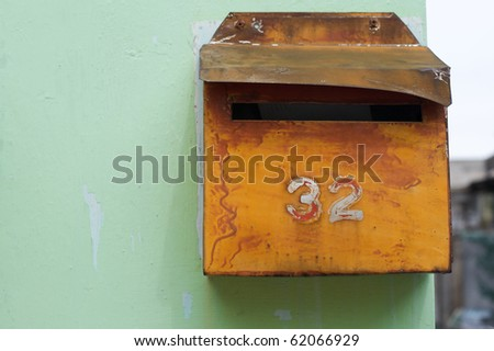Retro style letterbox against wall with number - stock photo