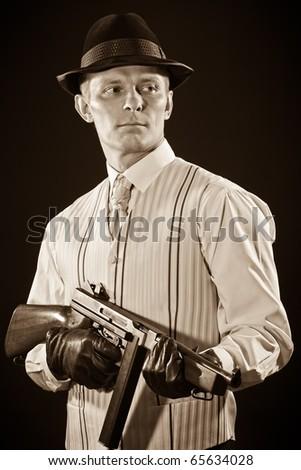 Retro style - Man keeps a submachine gun in sepia tone - stock photo