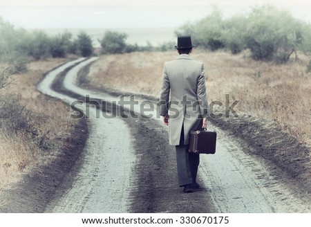 Retro style man on the country road, view from back - stock photo