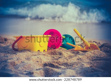 Retro Style Photo Of Children's Toys On A Beach With Waves In The Background - stock photo