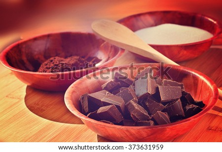 Retro style photo of food ingredients for baking. Dark chocolate chunks, cocoa powder and caster sugar in brown bamboo bowls and a wooden spoon. Toned image. Selective focus - stock photo