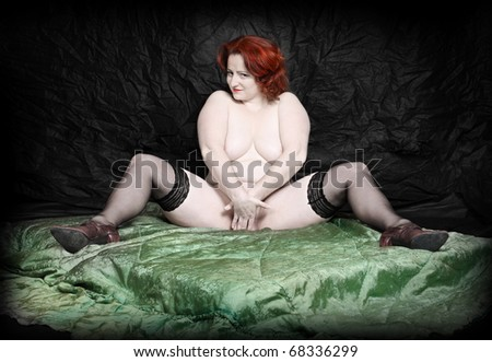 Retro style picture of a overweight woman posing on a green blanket. - stock photo