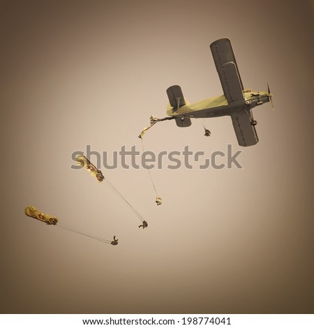 Retro style picture of the biplane with skydivers.  - stock photo