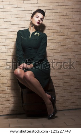 Retro Style. Pin-up Girl sitting in Green Dress on Barrel over Brick Brown Wall - stock photo