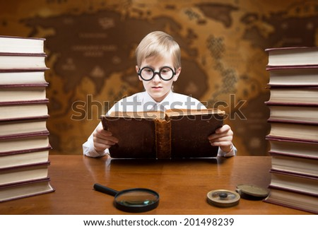 Retro style portrait of a reading boy against an old world map - stock photo