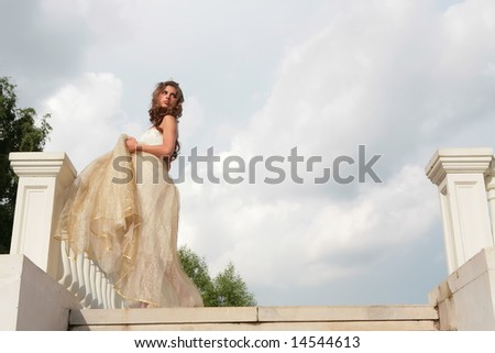 retro style  portrait of the beautiful girl in white gown on background cloudy sky - stock photo