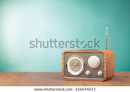 Retro style radio receiver on table in front mint green background - stock photo